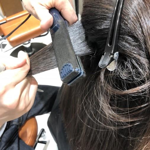 波状毛にアイロンをあてている画像