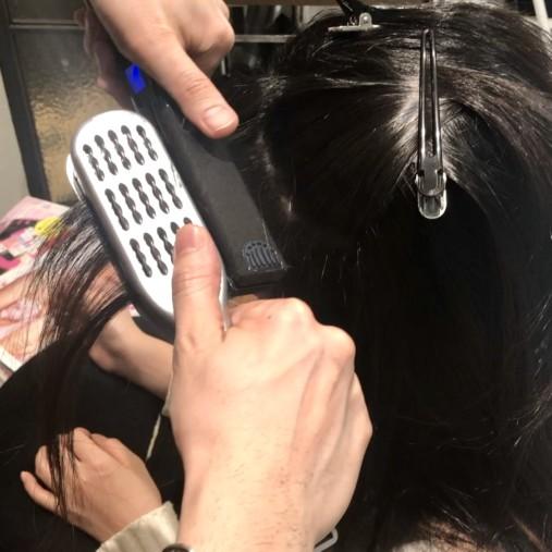 捻転毛をアイロンで伸ばしている画像